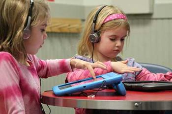 Two girls playing KinderTEK on iPads