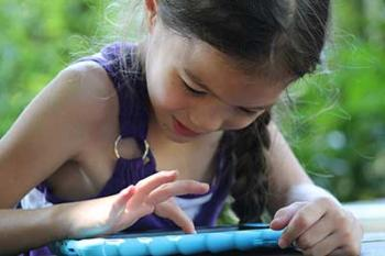 Dark haired girl playing KinderTEK on an iPad